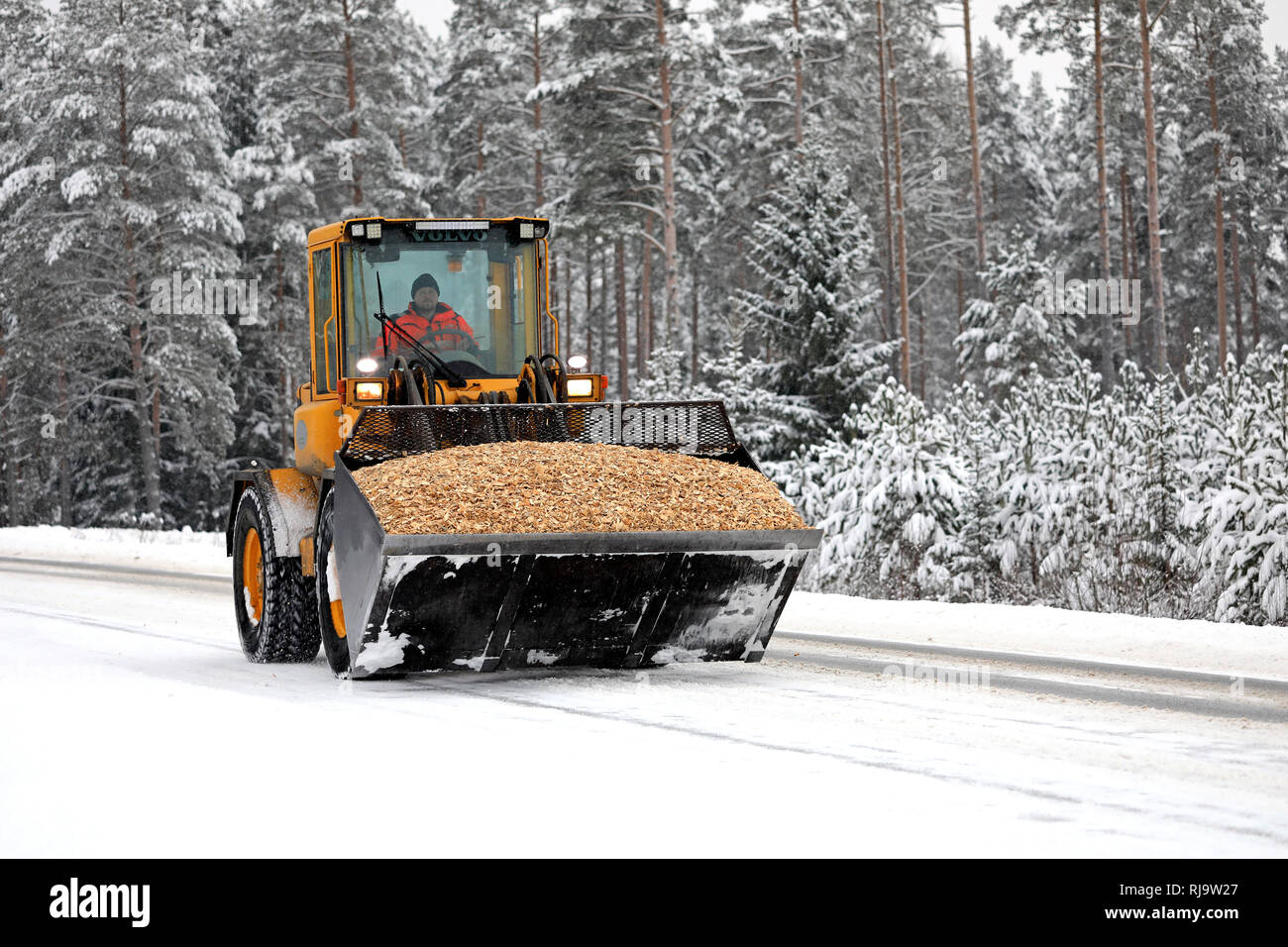 Salo, Finland - January 25, 2019: Volvo wheel loader operator transports a neat load of woodchip in the bucket attachment along snowy lane in winter. - Stock Image