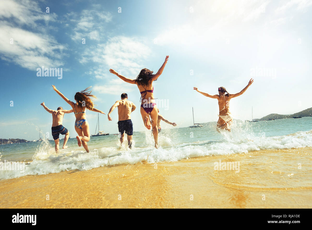 Big group of friends runs at sea beach. Tropical vacations concept Stock Photo