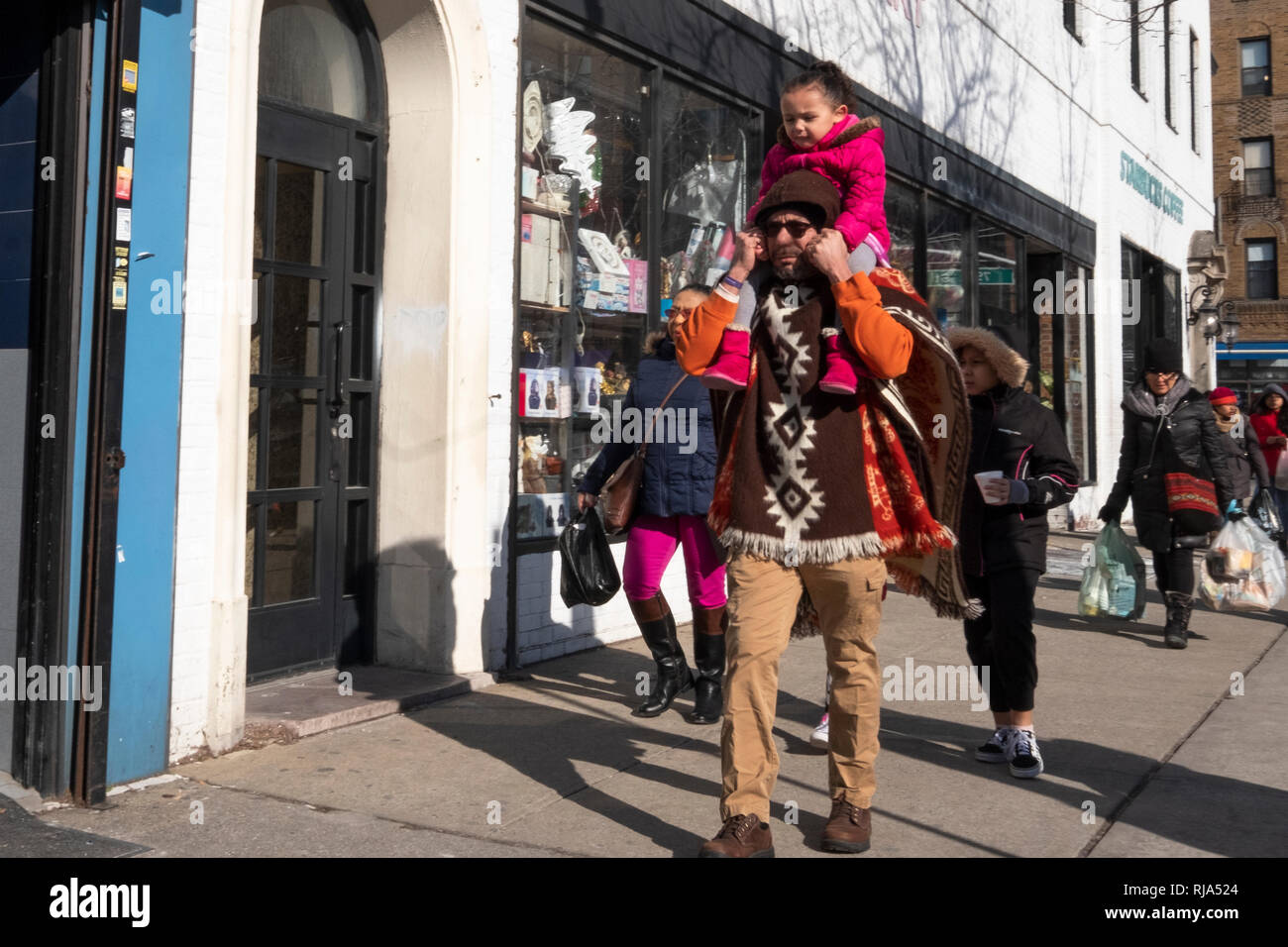 A busy street scene on 37th Avenue in Jackson Heights featuring a father carrying his daughter on his shoulders. In Queens, New York City. - Stock Image