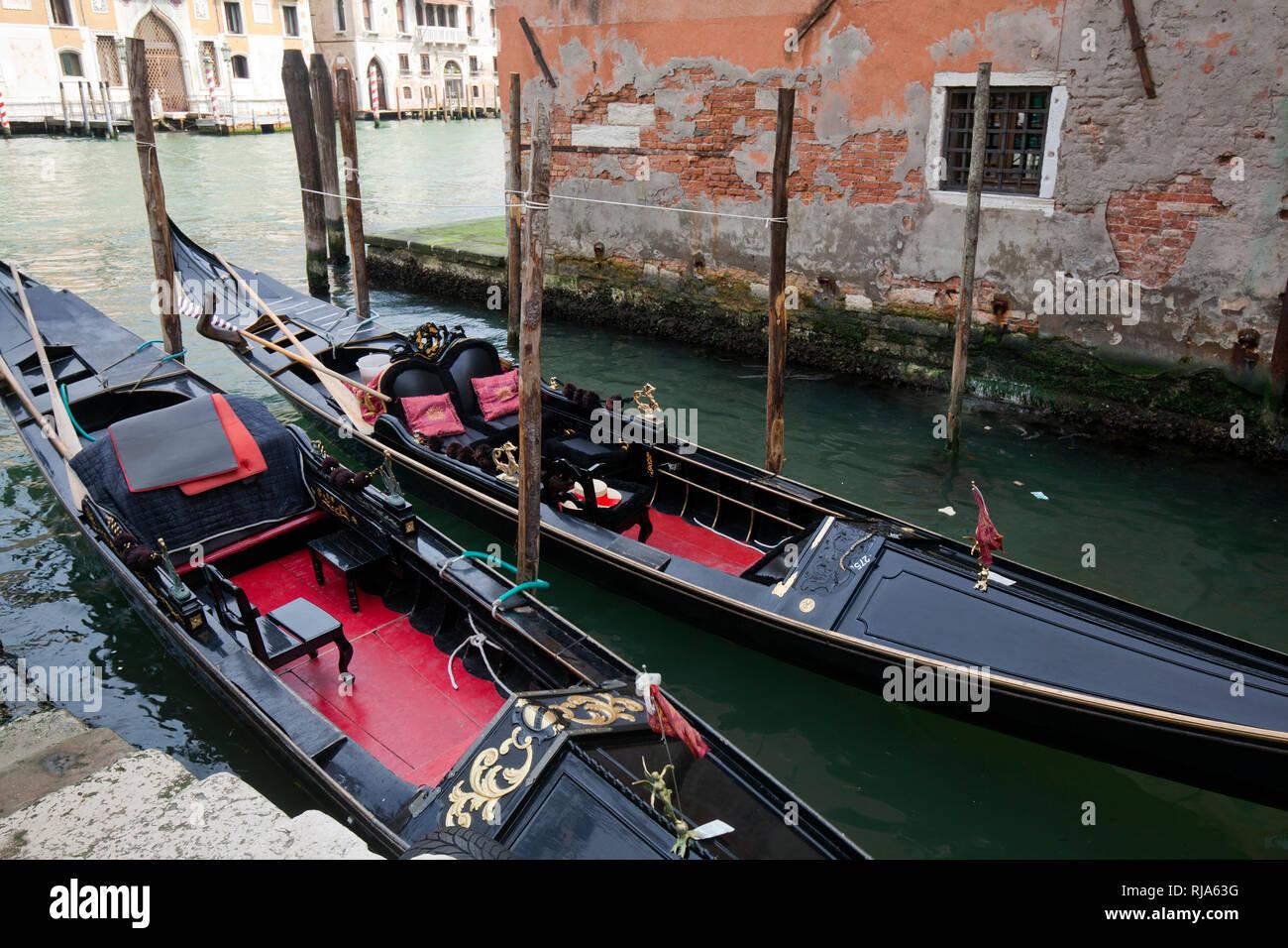 zwei schwarze Gondeln liegen in schmalem Kanal in Venedig - Stock Image