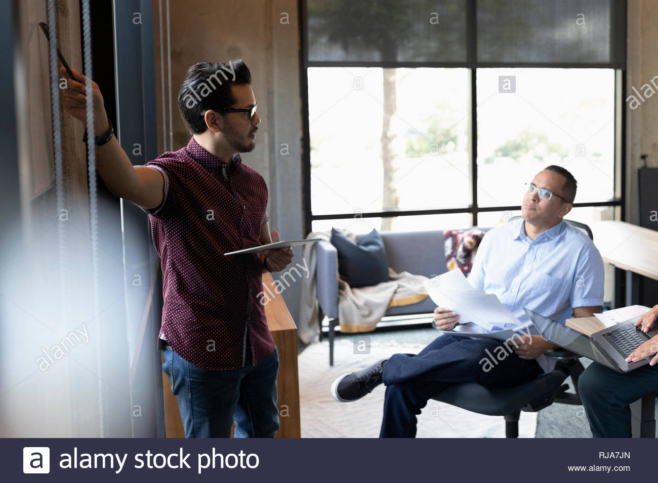 businessmen strategizing in office meeting - Stock Image