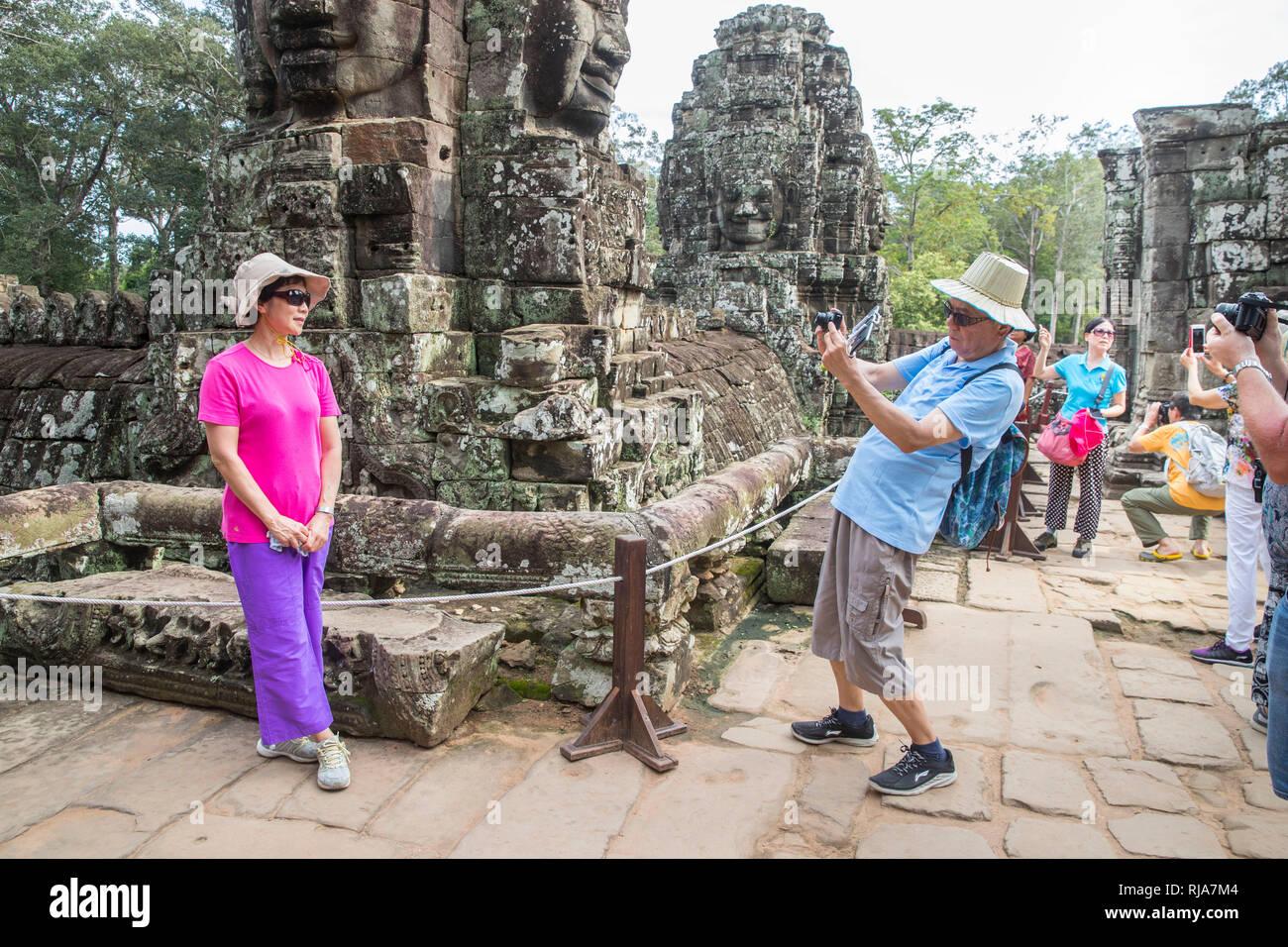 Siem Reap, Angkor, Tempel Bayon, von Touristen überlaufen, Paar beim fotografieren - Stock Image