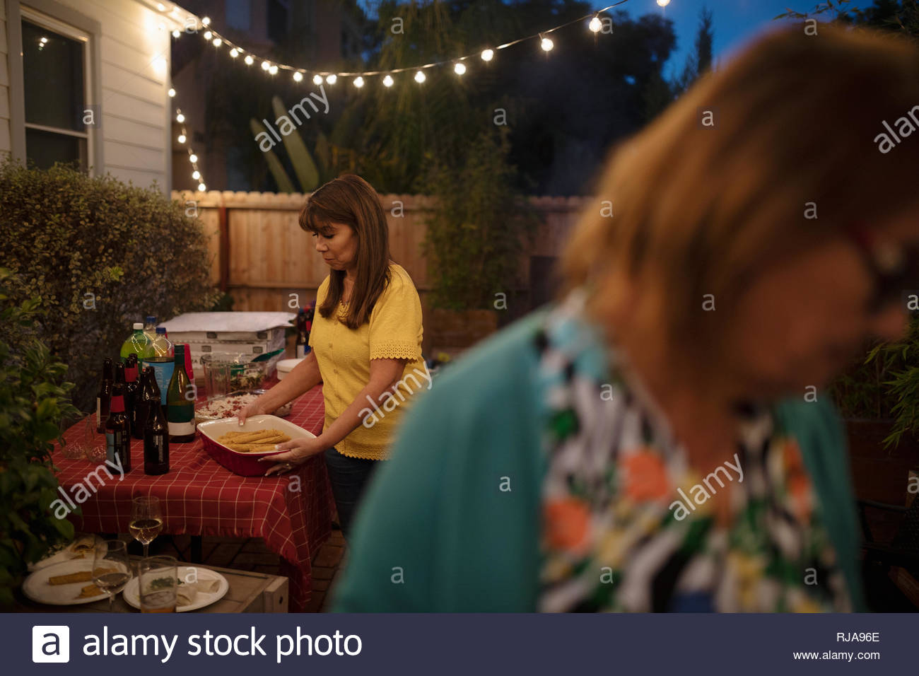 Latinx woman cleaning up after patio barbecue - Stock Image
