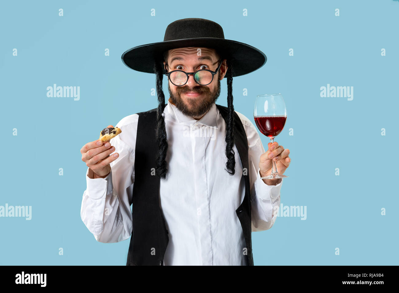 The young orthodox Jewish man with black hat with Hamantaschen cookies for Jewish festival of Purim at studio. The purim, jewish, festival, holiday, celebration, judaism, pastry, tradition, cookie, religion concept - Stock Image