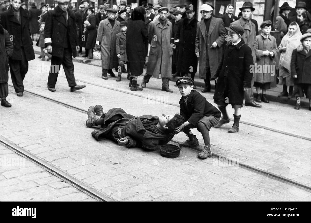 A young Jewish boy helps a man who fell on Tram Tracks, in the Warsaw Ghetto; Warsaw, Poland. The Warsaw Ghetto, was the largest of all the Jewish ghettos in German-occupied Europe during World War Two. It was established by the German authorities in 1940; within the new General Government territory of German-occupied Poland. There were over 400,000 Jews imprisoned there. - Stock Image
