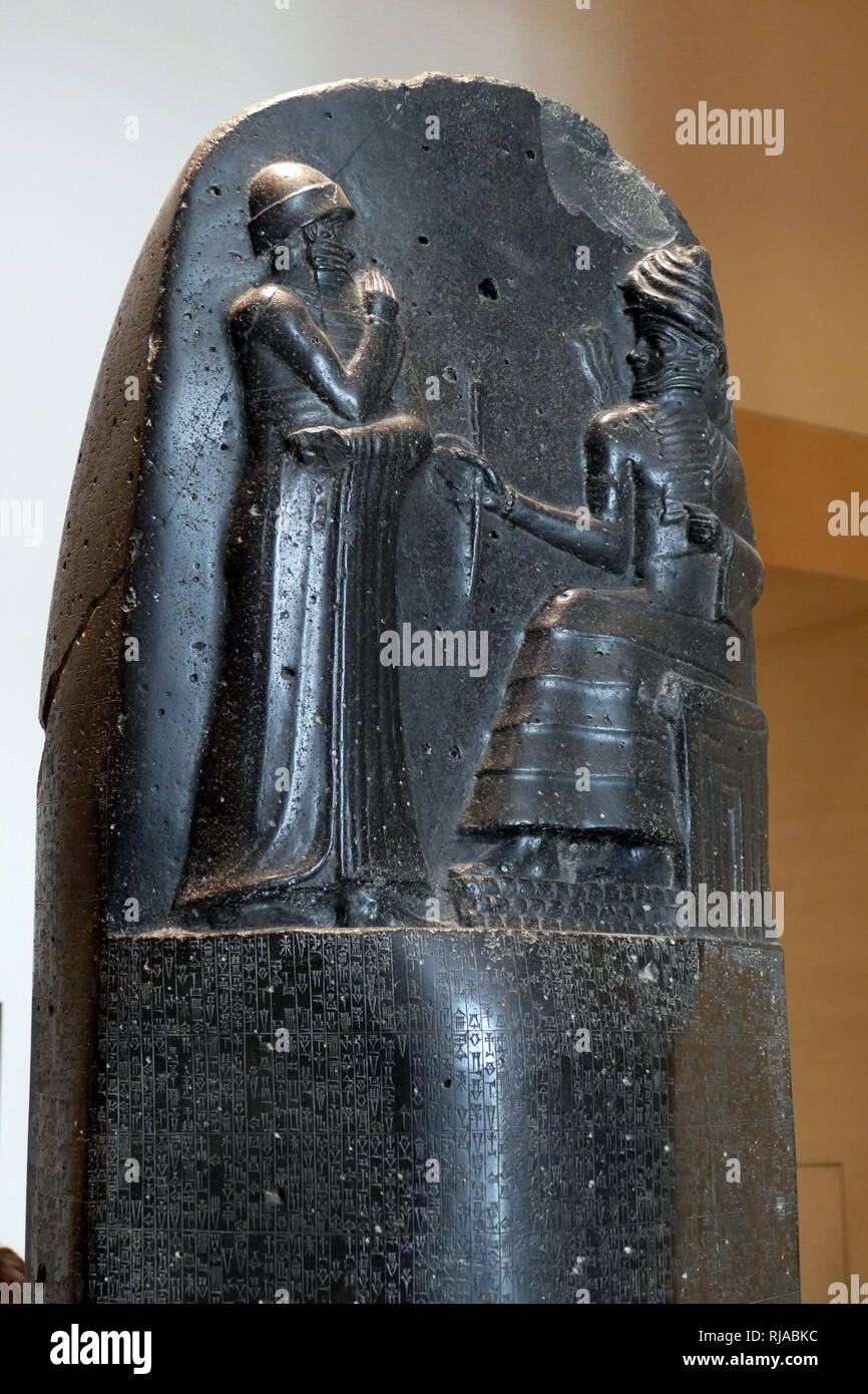 Stele in Black Basalt depicting the Code of Hammurabi; 1792-1750 BC. Hammurabi's code was a Babylonian body of written law for ancient Mesopotamia. At the top of the stele is Hammurabi (standing), depicted receiving his royal insignia from Shamash (or possibly Marduk). Hammurabi holds his hands over his mouth as a sign of prayer - Stock Image