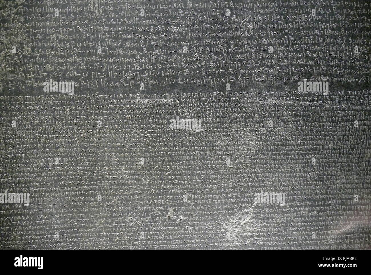 Detail from the Rosetta stone showing Demotic and Greek texts. The Rosetta Stone is a granodiorite stele, dating to 196 BC, found in 1799. It is inscribed with three versions of a decree issued at Memphis, Egypt, during the Ptolemaic dynasty on behalf of King Ptolemy V. The top and middle texts are in Ancient Egyptian using hieroglyphic script and Demotic script, respectively, while the bottom is in Ancient Greek. As the decree has only minor differences between the three versions, the Rosetta Stone proved to be the key to deciphering Egyptian hieroglyphs. Study of the decree was already under - Stock Image