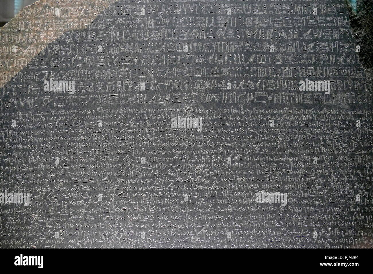 Detail from the Rosetta stone showing hieroglyphic and Demotic texts. The Rosetta Stone is a granodiorite stele, dating to 196 BC, found in 1799. It is inscribed with three versions of a decree issued at Memphis, Egypt, during the Ptolemaic dynasty on behalf of King Ptolemy V. The top and middle texts are in Ancient Egyptian using hieroglyphic script and Demotic script, respectively, while the bottom is in Ancient Greek. As the decree has only minor differences between the three versions, the Rosetta Stone proved to be the key to deciphering Egyptian hieroglyphs. Study of the decree was alread - Stock Image