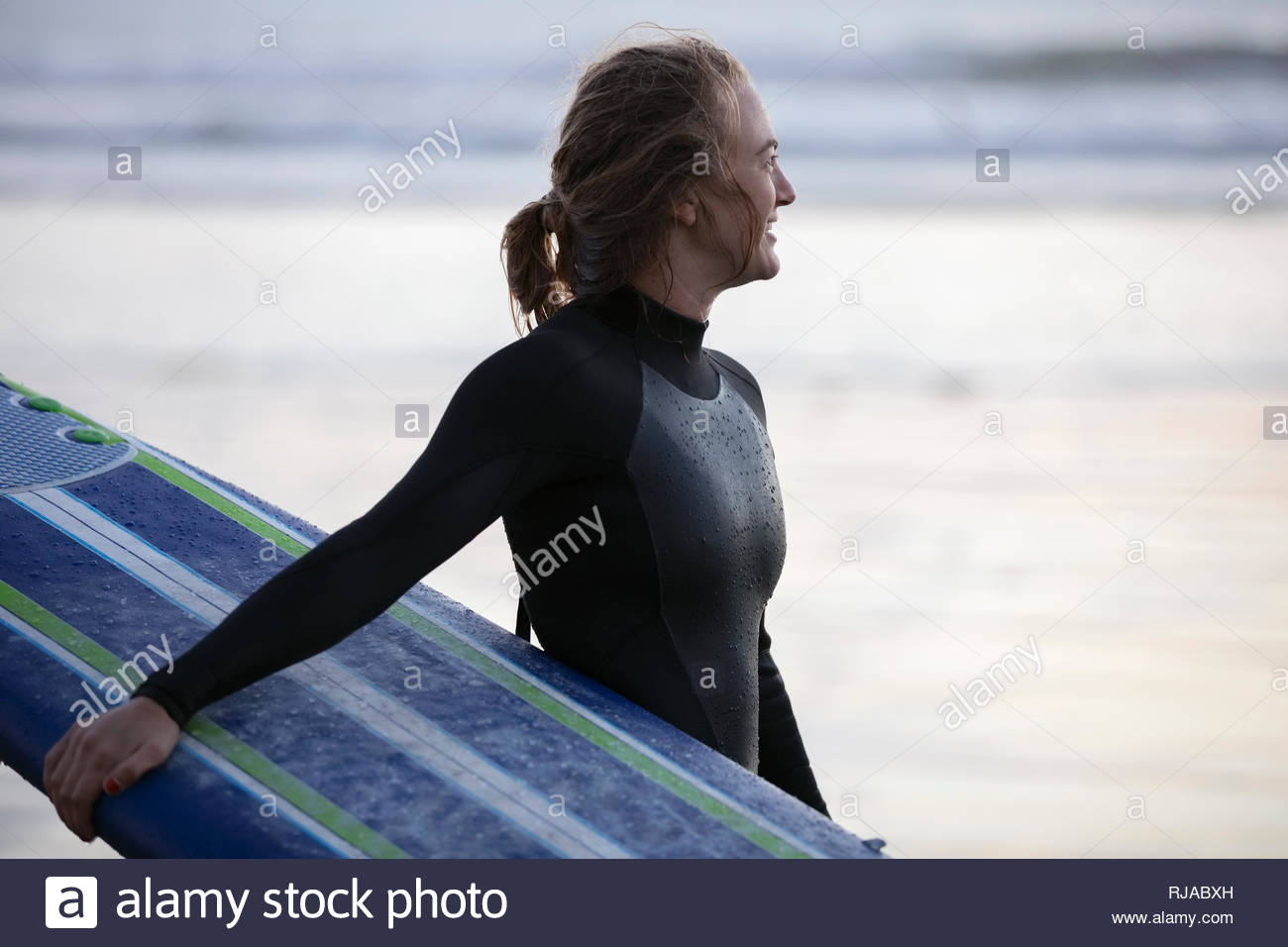 Female surfer in wet suit holding surfboard on beach - Stock Image