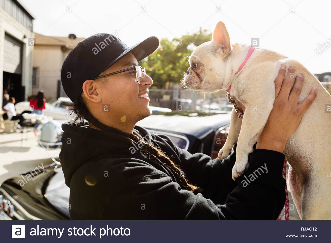 Latinx young man holding French bulldog in sunny parking lot - Stock Image