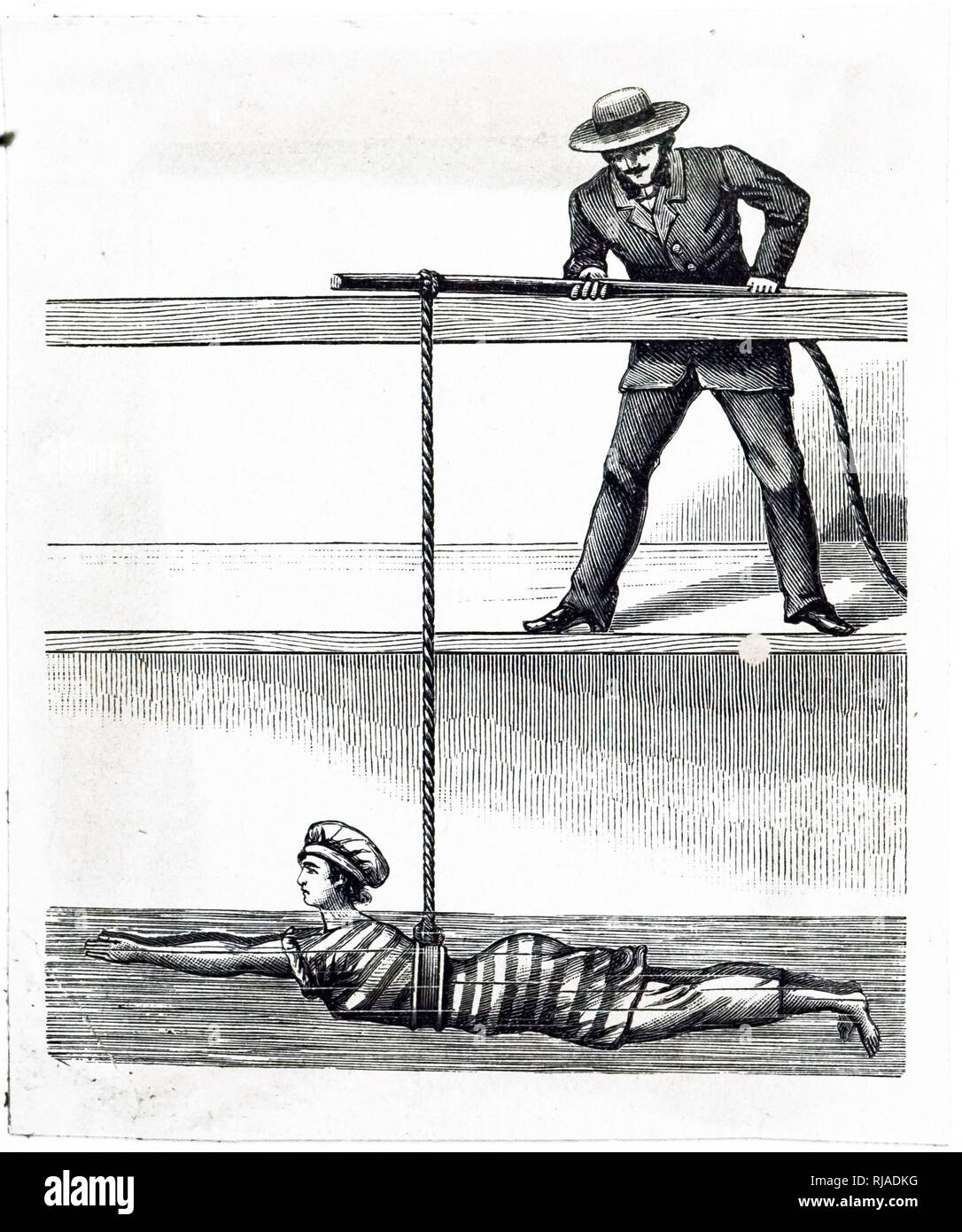 An engraving depicting a man teaching a woman how to swim. He has tied one end of a rope around her waist and the other around a pole which he holds up to keep the swimmer afloat. Dated 19th century Stock Photo