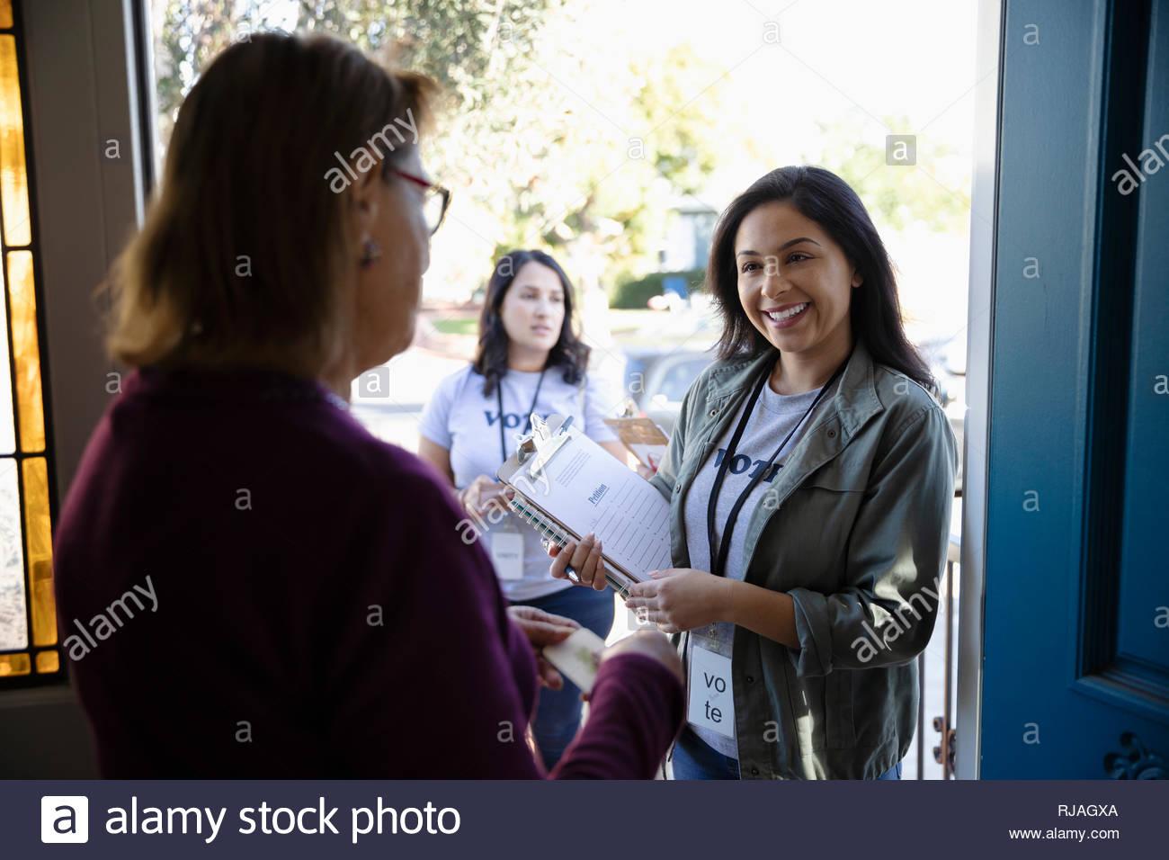 Latinx female volunteer canvassing voters door-to-door - Stock Image