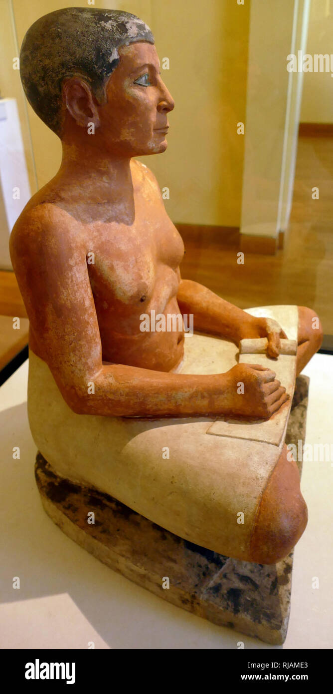 The sculpture of the Seated Scribe or Squatting Scribe is a famous work of ancient Egyptian art. It represents a figure of a seated scribe at work. The sculpture was discovered at Saqqara, north of the alley of sphinxes leading to the Serapeum of Saqqara, in 1850 and dated to the period of the Old Kingdom, from either the 5th Dynasty, c. 2450-2325 BCE or the 4th Dynasty, 2620-2500 BCE. It is now in the Louvre Museum in Paris. - Stock Image