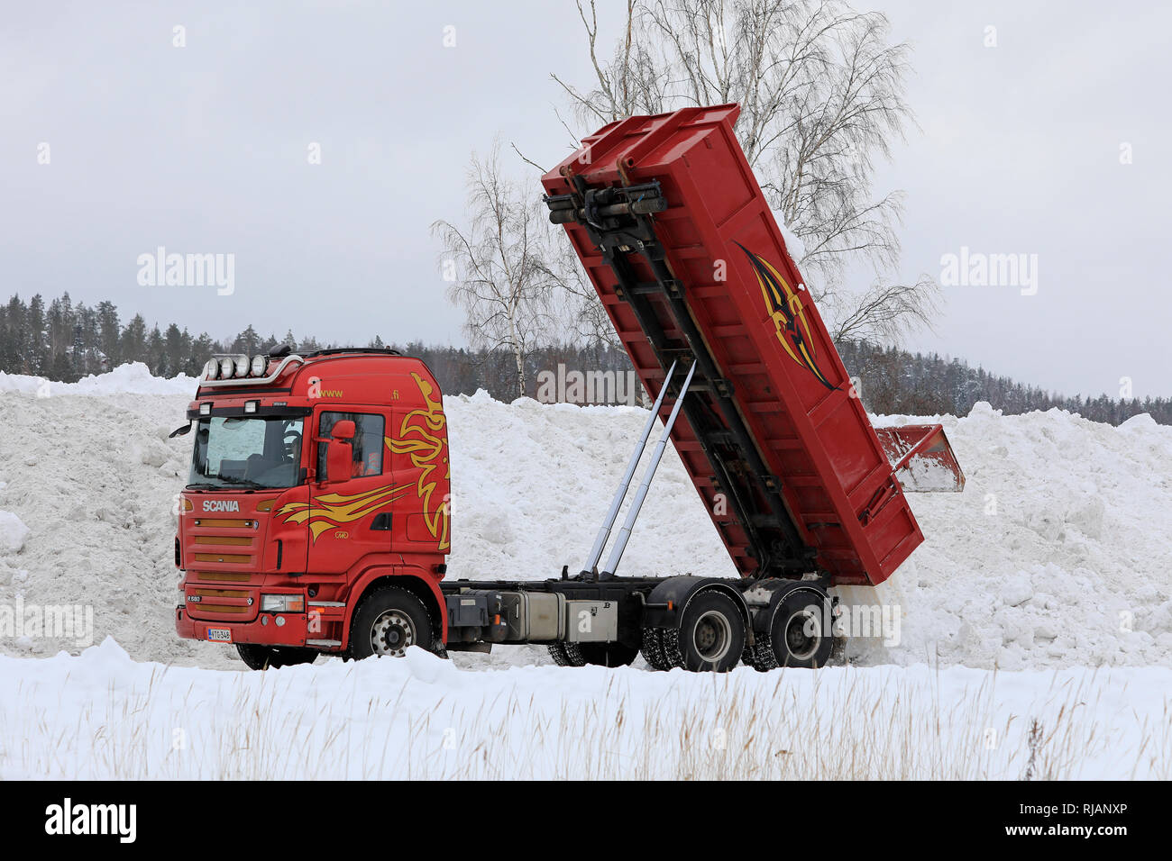 Salo, Finland - February 2, 2019: Red Scania R580 tipper truck unloads snow cleared from streets and parking lots at municipal snow dumping area. - Stock Image