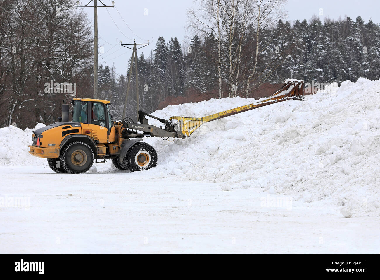 Salo, Finland - February 2, 2019: Volvo L45F wheel loader with snow handling attachment at work at municipal snow dumping area in South of Finland. - Stock Image