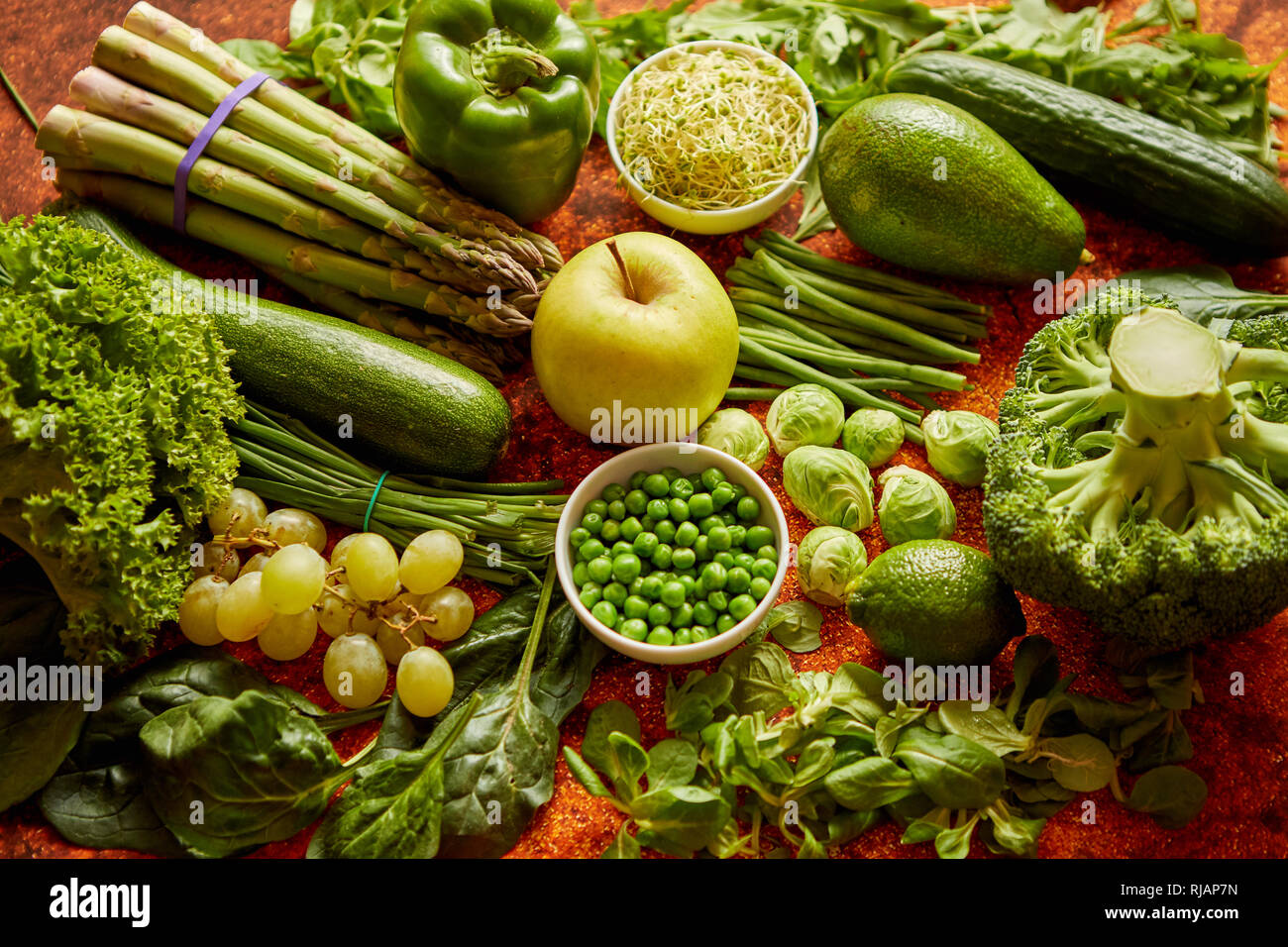 Fresh green vegetables and fruits assortment placed on a rusty metal Stock Photo