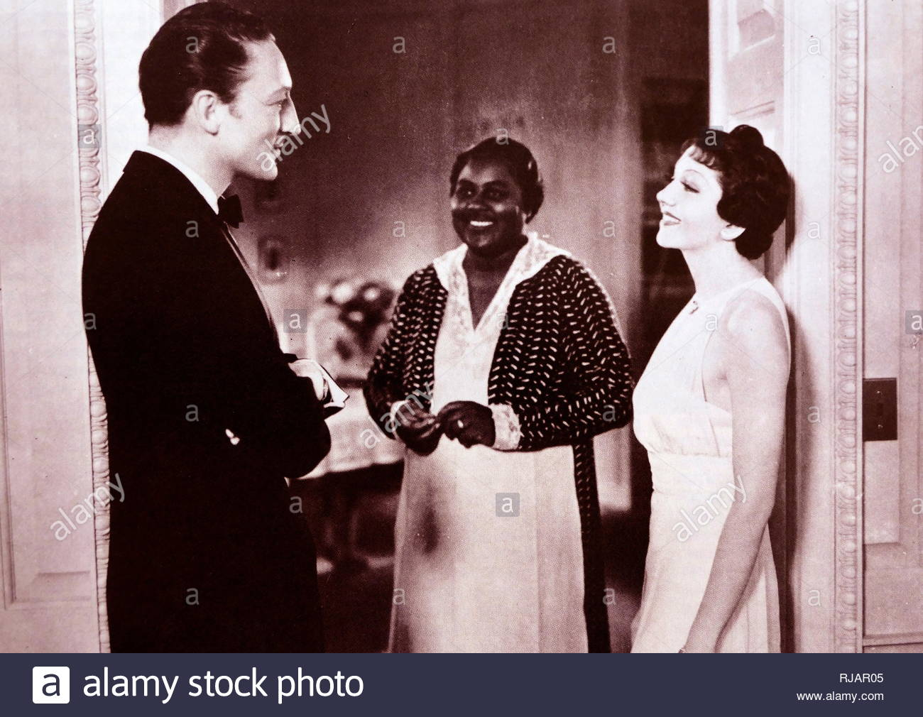 Imitation of Life is a 1934 American drama film directed by John M. Stahl. The screenplay by William Hurlbut, based on Fannie Hurst's 1933 novelo. The film stars Claudette Colbert, Warren William. In this scened Hattie McDaniel  appears with Warren William and Claudette Colbert. Mc Daniel was a pioneer African American actress - Stock Image