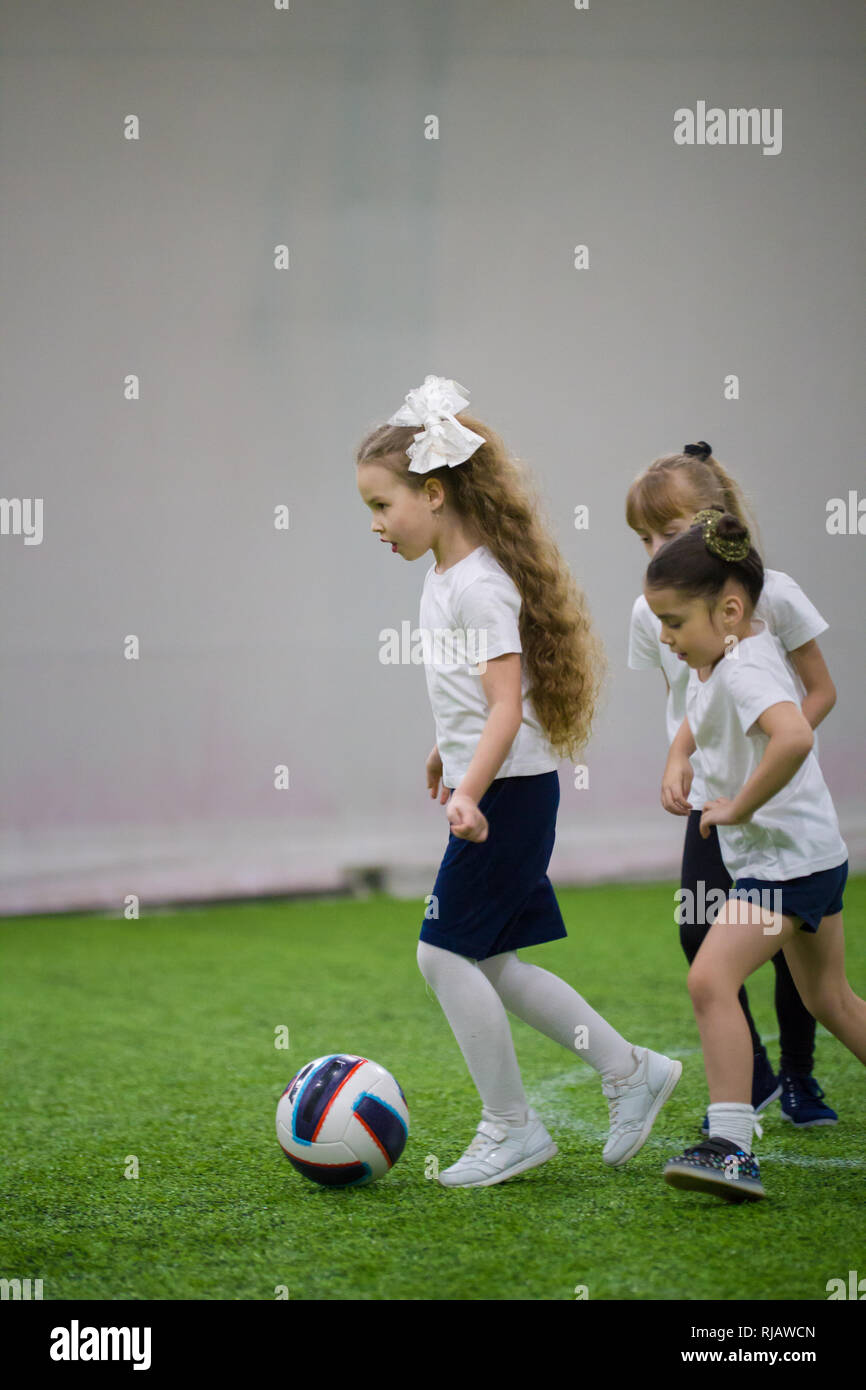 Playing football indoors. A little girl leads the ball - Stock Image