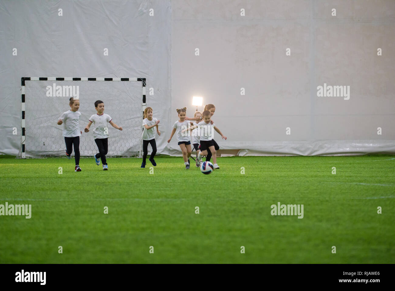 Football arena indoors. Children team playing football - Stock Image