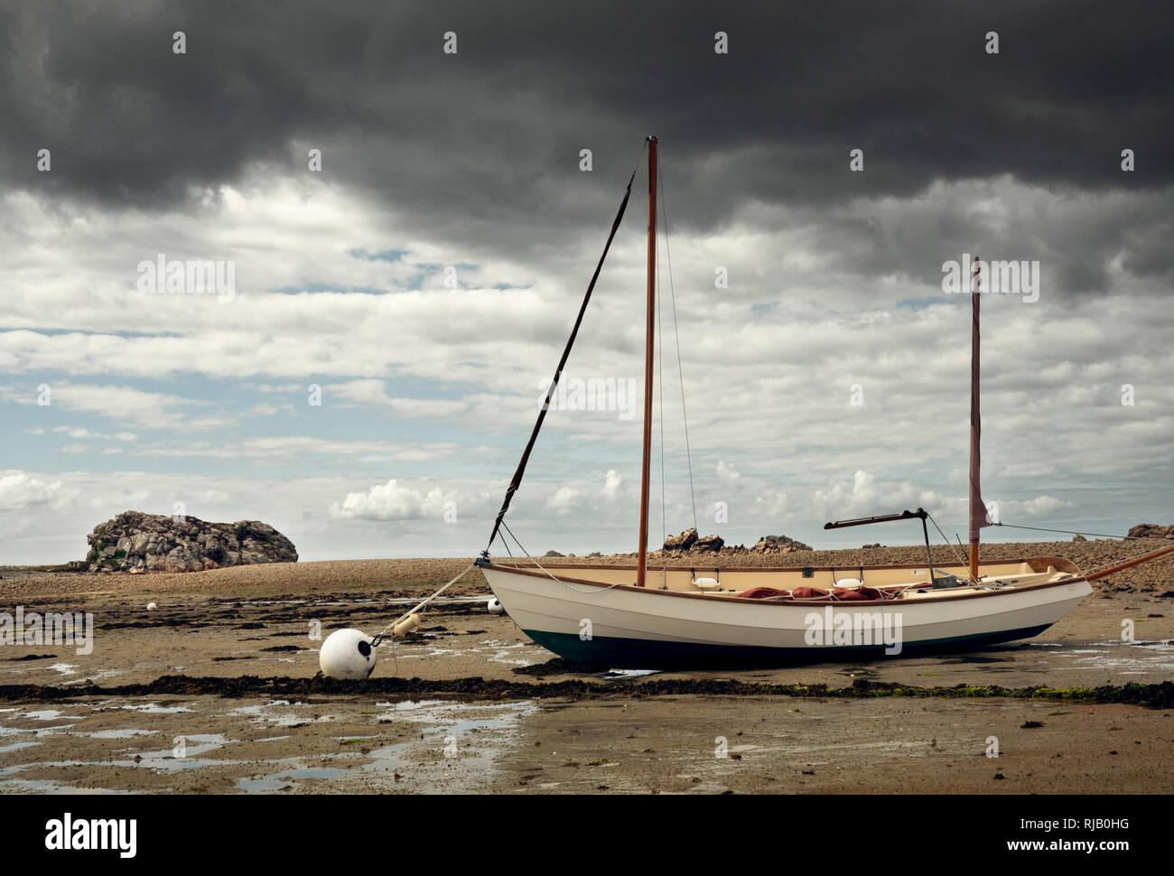Durch die Ebbe trocken gelegtes Segelboot in der Bretagne - Stock Image