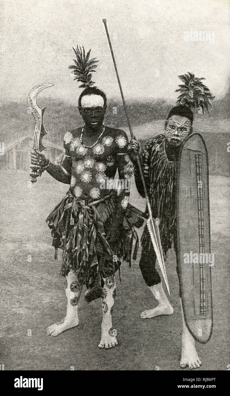 Spearman and battle axeman in magic warpaint, Belgian Congo (now Democratic Republic of the Congo), Central Africa. - Stock Image