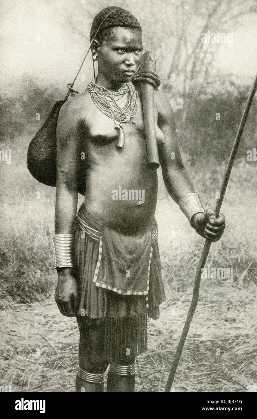 Watuta (possibly Watutsi, Watusi, Tutsi) woman, carrying a bag slung by a string across the top of her head, and an axe across her shoulder, south-east of Lake Tanganyika, East Africa (then part of the British Empire, now Tanzania). Stock Photo