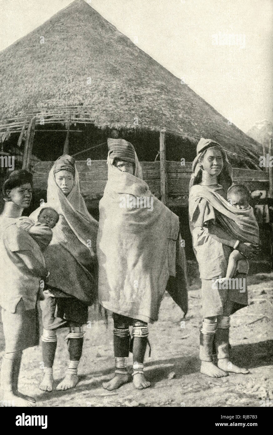 Women of the Padaung (Kayan Lahwi or Lahoi) tribe, Burma (now Myanmar), South East Asia. Two of them can be seen with brass coils round their necks. They are wrapped in blankets because of cold weather. Stock Photo