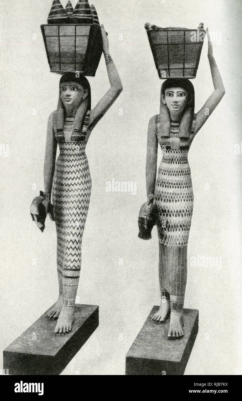 Wooden statues of handmaidens with baskets on their heads, discovered near Thebes during excavations, Egypt. Their purpose was to minister to the needs of the dead inside a pyramid. Stock Photo