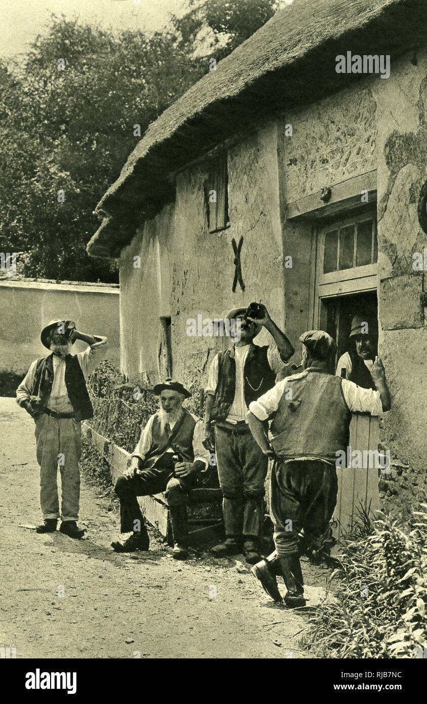 Men drinking beer after a day's work, haymaking in the fields, in the West Country village of Bradford Peverell, Dorset, an English county which inspired the writings of the novelist Thomas Hardy and the poet William Barnes. Stock Photo