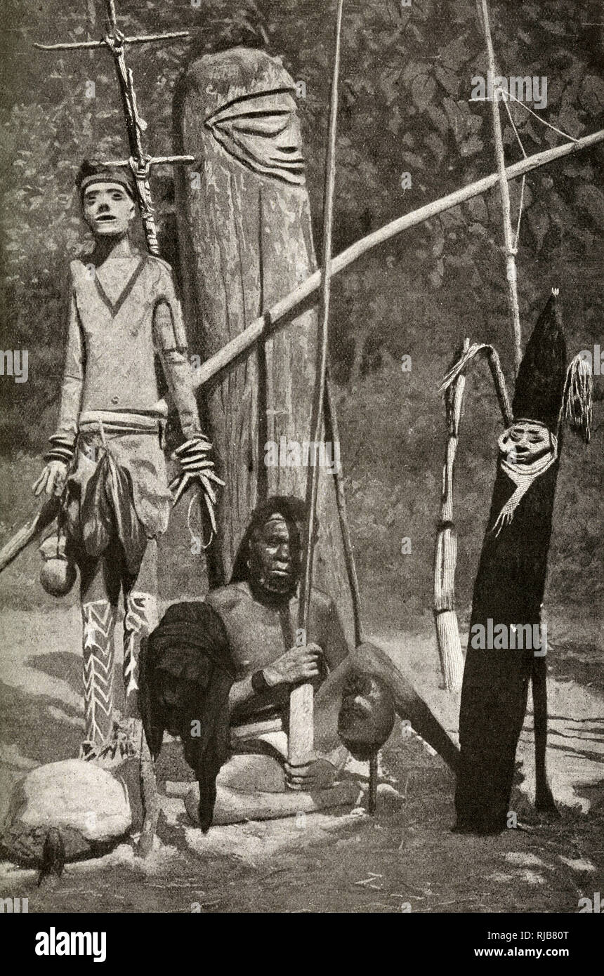 Melanesian man of the French New Hebrides, South Pacific (now Vanuatu). He is surrounded by precautions against the power of evil spirits - the embalmed body of one of his ancestors (left), and trophies in front of him from enemies he has killed. - Stock Image