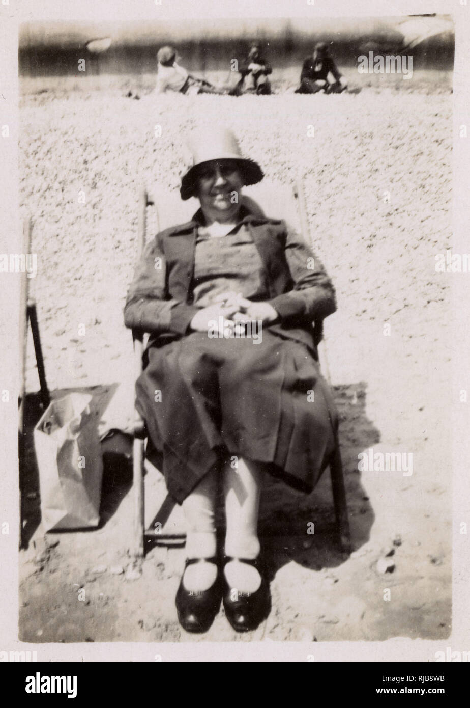 A woman called June looking very comfortable and organised in a deckchair on an unidentified beach. Stock Photo
