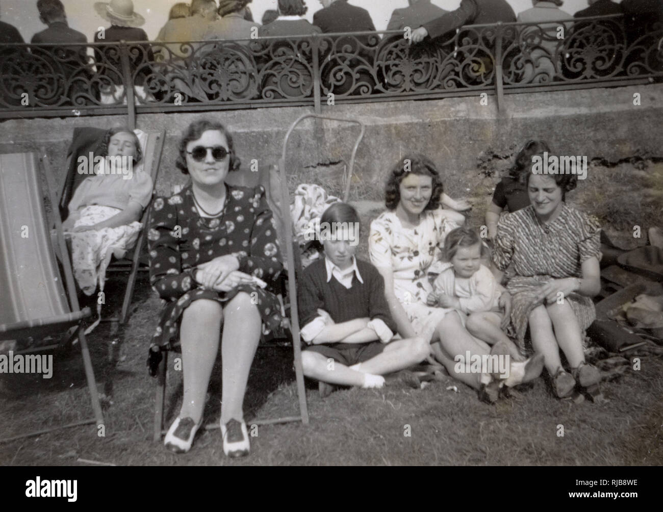 A family relaxing on the beach at an unidentified seaside resort.  Behind them, can be seen the backs of other people lined up on benches along a promenade. - Stock Image