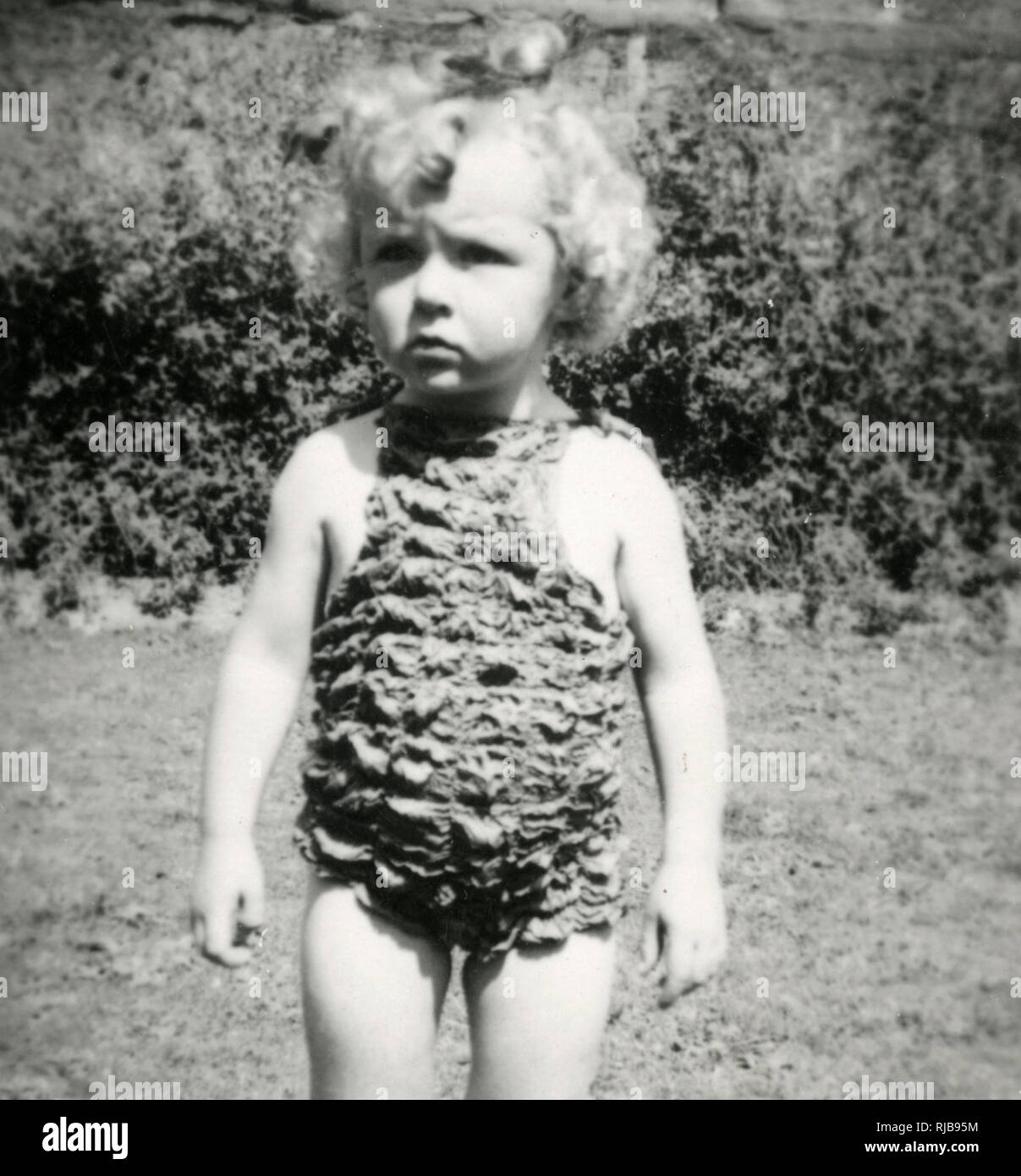 A little girl wearing a rather bizarre crimpled swimsuit Stock Photo