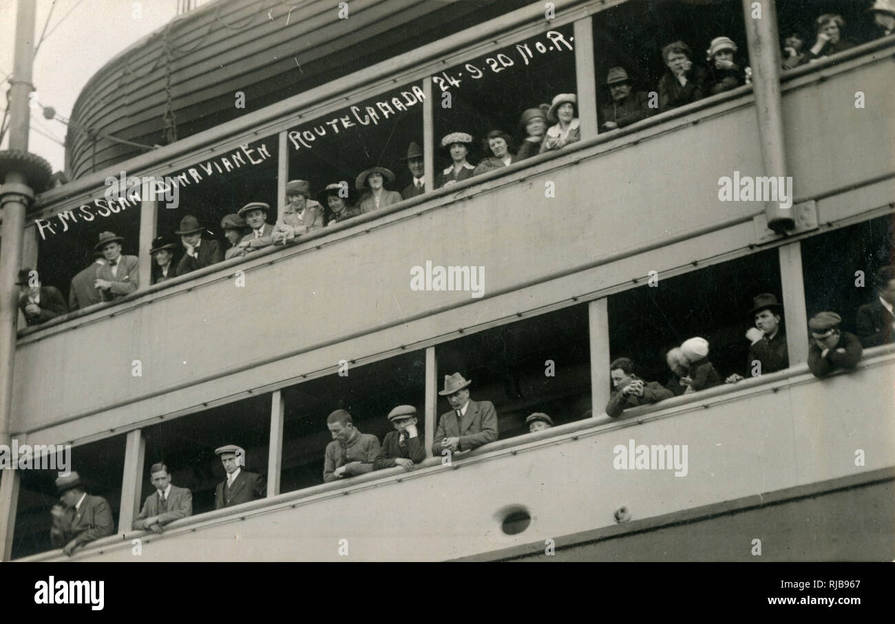 Passengers on the rail of the RMS Scandinavian en route to Canada - 24th September 1920. Stock Photo