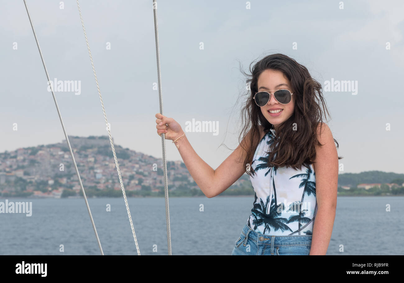 Young teen girl with sunglasses on deck of sailboat in bathing suit - Stock Image