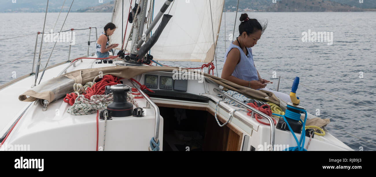Mother and daughter with cell phones sitting on the deck of a sailboat that is sailing - Stock Image