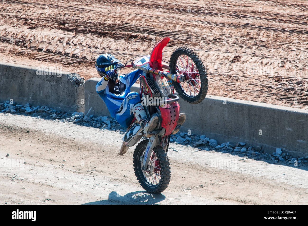 Goshen, Connecticut.  September 4, 2017.  A man wearing a racing gear and a helmut pulling a wheelie on a dirt bike at the Goshen Fair in Goshen Conne - Stock Image