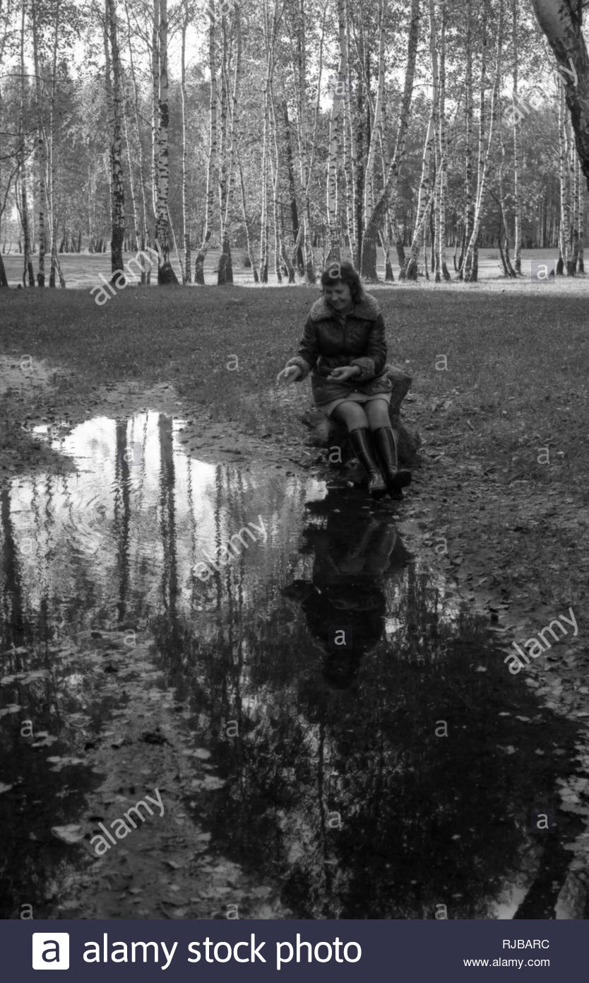 It is autumn forest after heavy rain. The large puddle formed on the forest road. The water reflects the trees. Near the puddle is sitting woman on a chair, who throws stones into water where appears circles. The visible silhouette of that women is seen in the puddle as well. There are a lot of young birches around. - Stock Image
