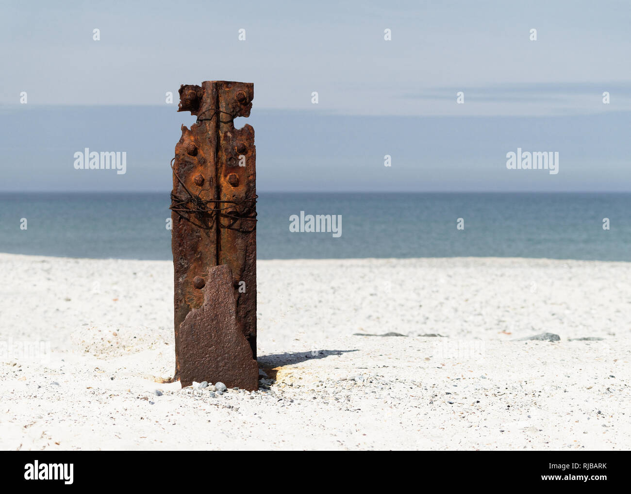 Rusty iron part as a remnant of buildings from the Second World War in the focus area on a bright sandy beach, behind blue sky and the sea - close-up, - Stock Image