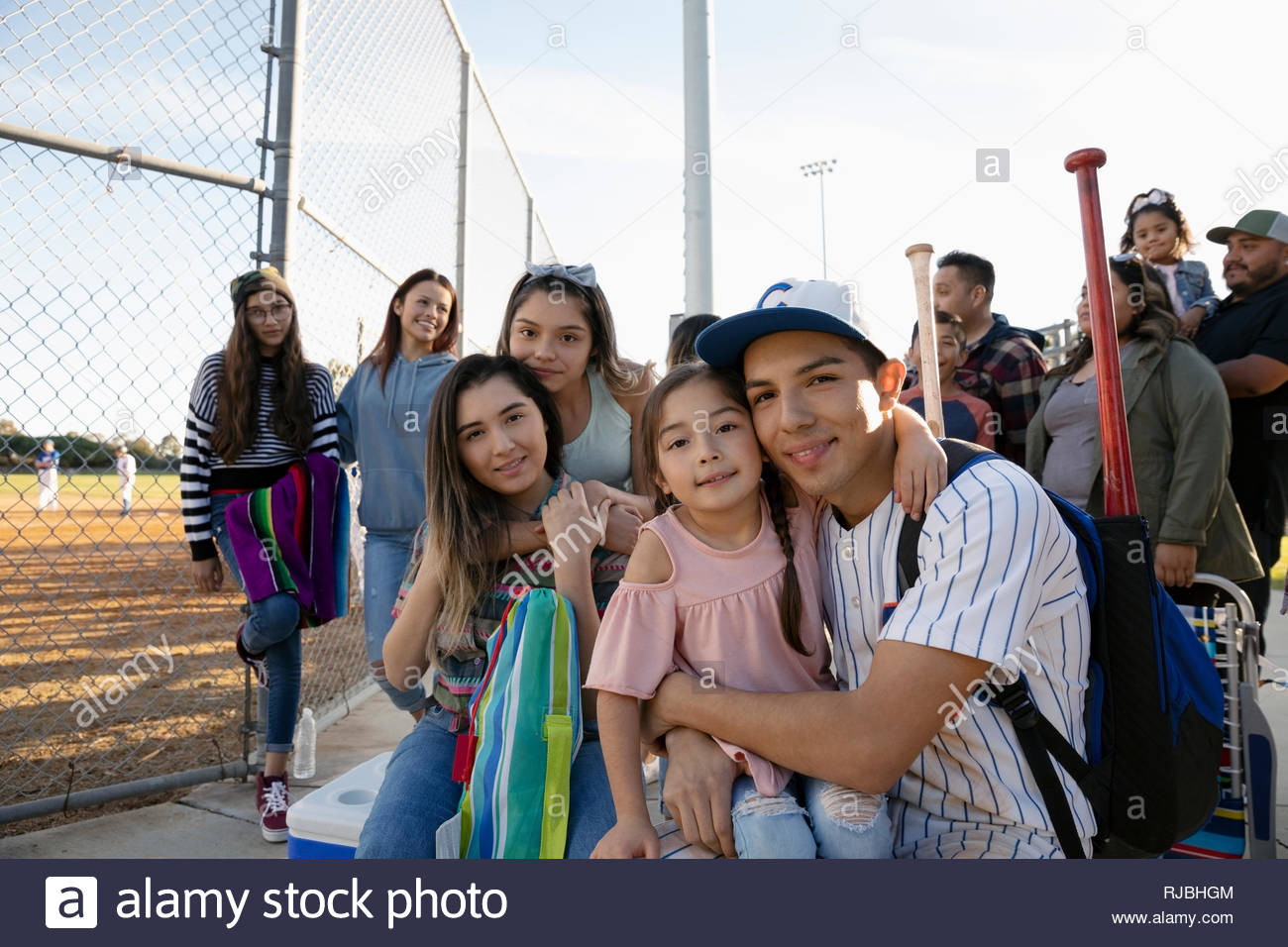 Portrait happy Latinx baseball player with family - Stock Image