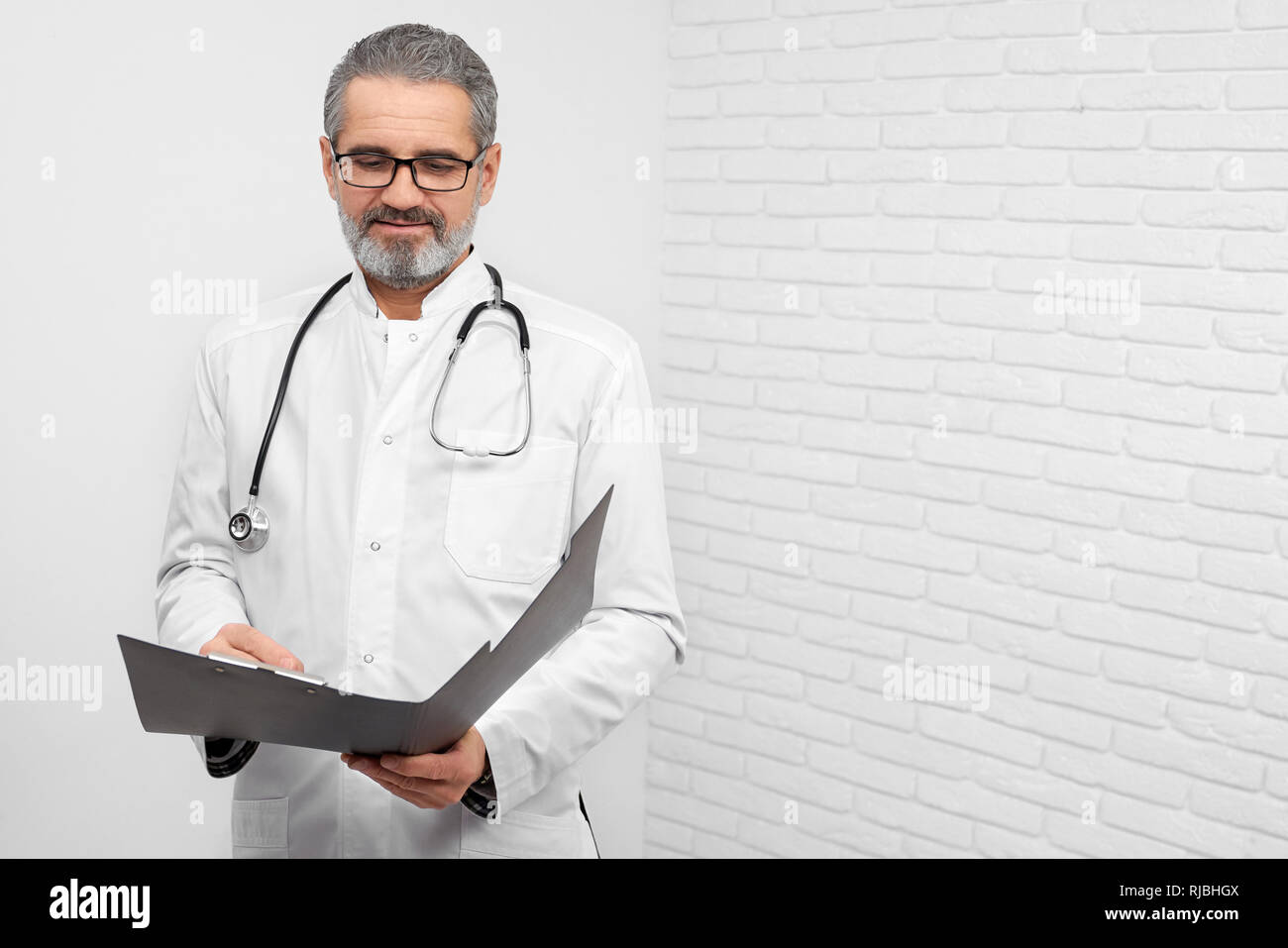 Professional ENT doctor standing in studio with white background. Mature, bearded doctor holding folder, looking down and reading. Physician having stethoscope on neck. - Stock Image