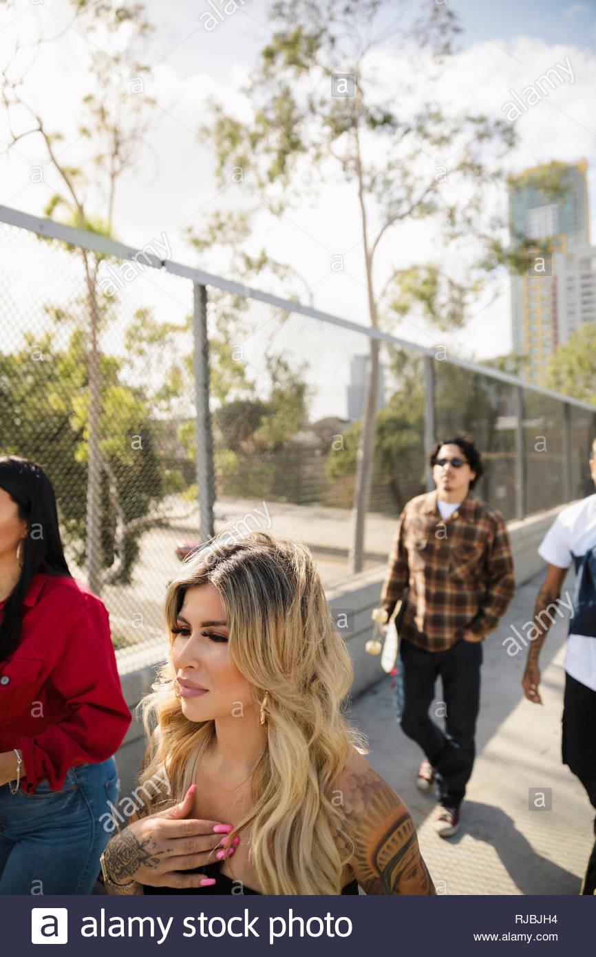 Latinx friends walking on urban sidewalk - Stock Image