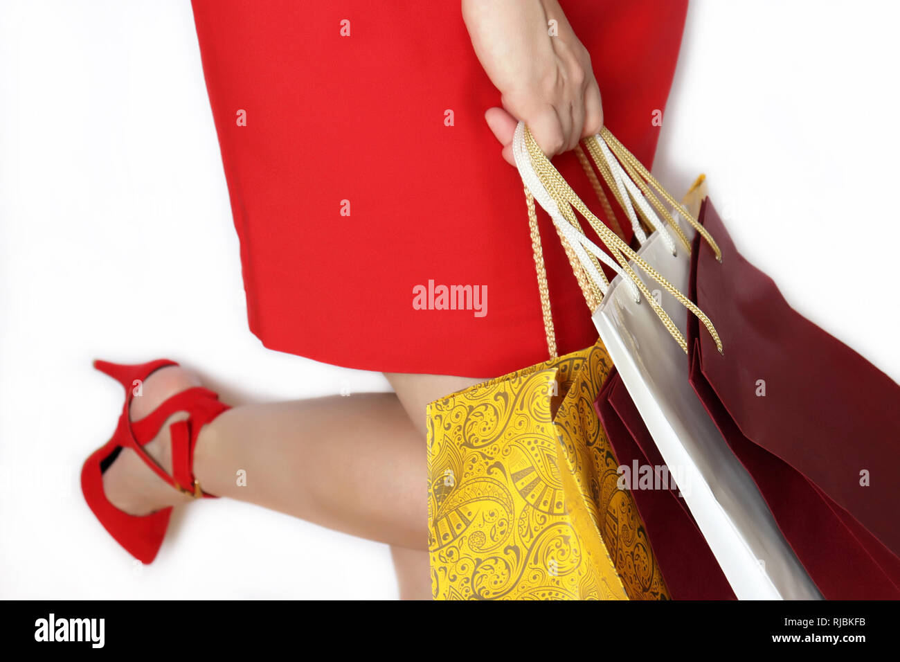 Woman with shopping bags on white background. Girl in red dress and shoes on high heels, concept of shopping, sale and gifts - Stock Image