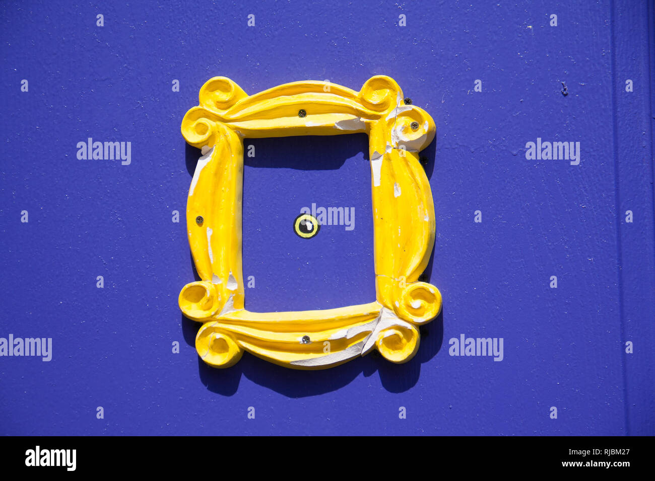 Yellow frame or peephole on blue door - Stock Image