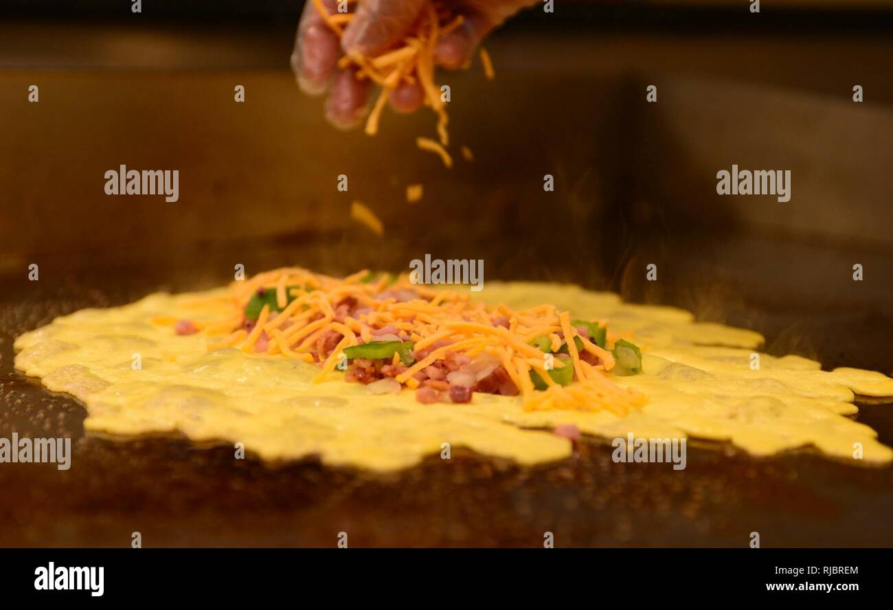 A ham and cheese omelet is prepared for a customer during the breakfast rush inside the Raider Café at Ellsworth Air Force Base, S.D., Jan. 12, 2018. Having won the Hennessey award several times in the past, an award recognizing the best dining facilities in the Air Force, food service personnel of the 28th FSS gear up to compete in this year's competition. Stock Photo