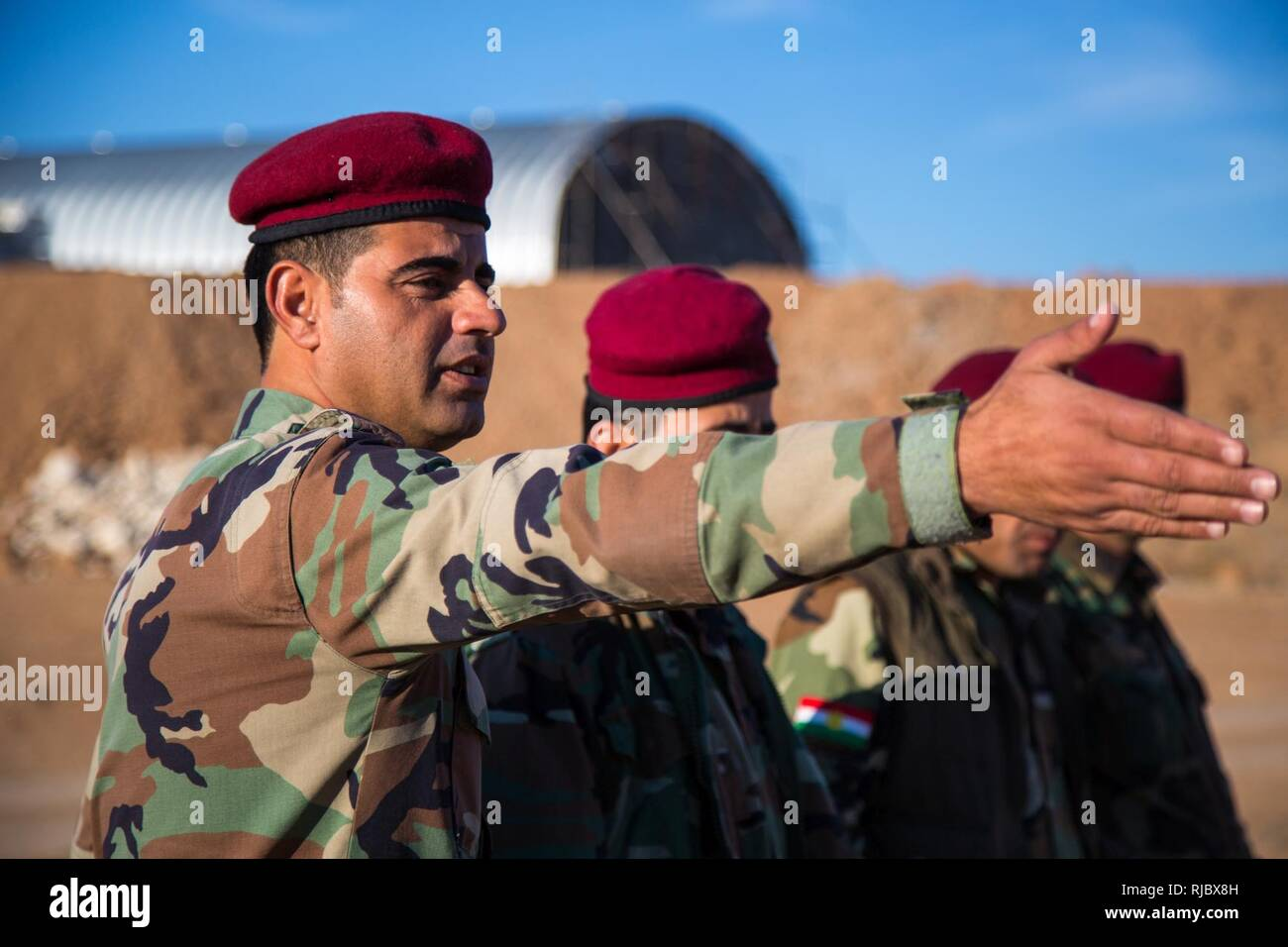 A coalition partner force member gestures towards his teammates during a counter improvised explosive device warm-up exercise at Erbil, Iraq, Jan. 10, 2018. This training is critical to enabling local security forces to secure their homeland from ISIS. CJTF-OIR is the global Coalition to defeat ISIS in Iraq and Syria. - Stock Image