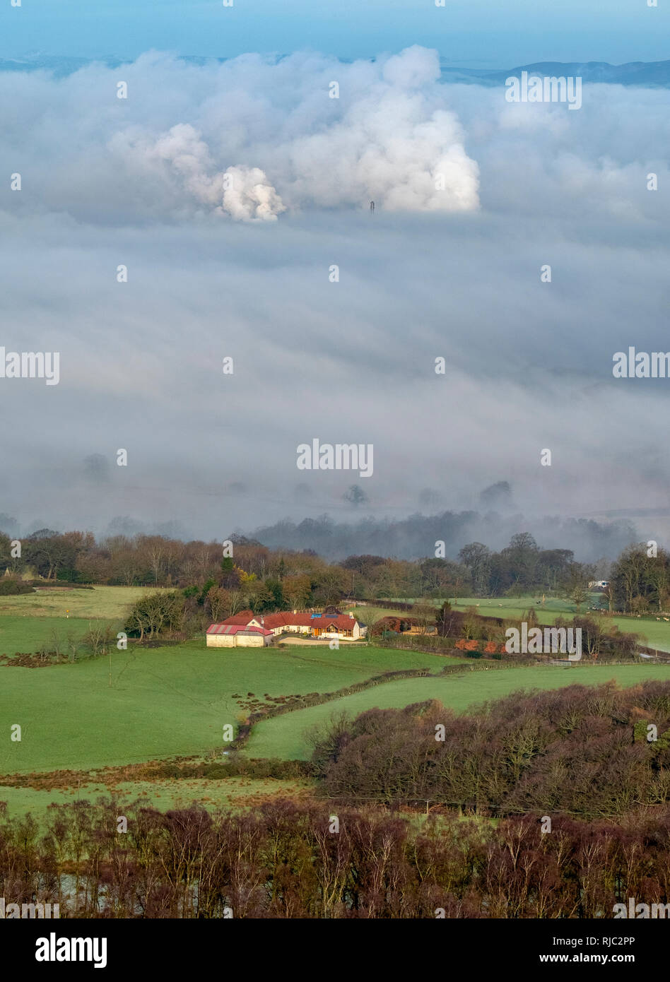 View of a farmhouse in the forth valley and showing emissions from the Grangemouth oil refinery in the distance showing through the morning mist. - Stock Image