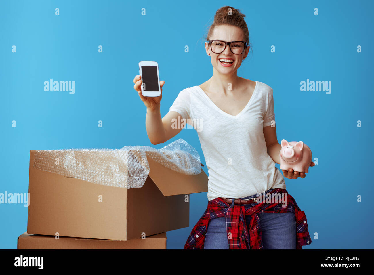 smiling young woman in white t-shirt with piggybank showing phone blank screen near cardboard box isolated on blue. Call professional movers and obtai - Stock Image