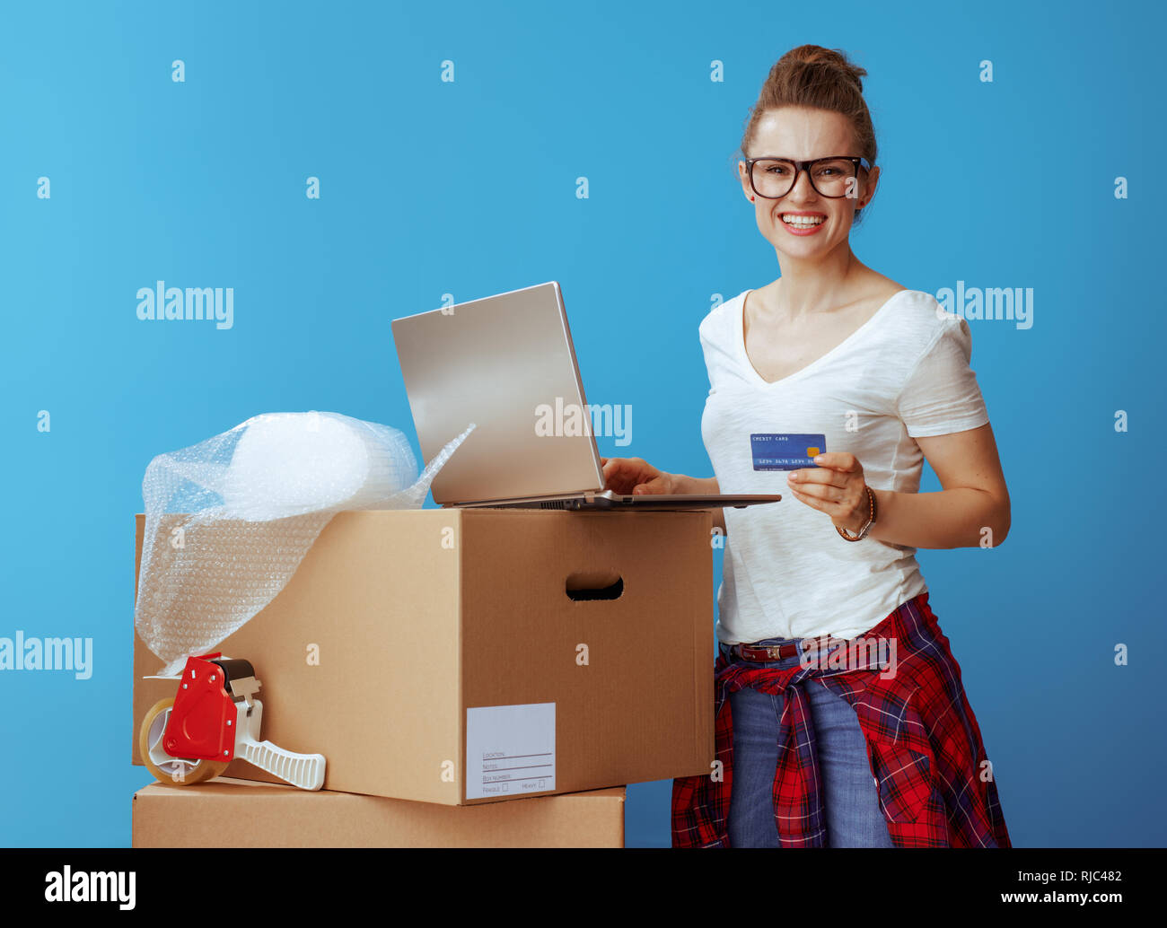 smiling modern woman in white t-shirt near cardboard box with laptop and credit card against blue background - Stock Image
