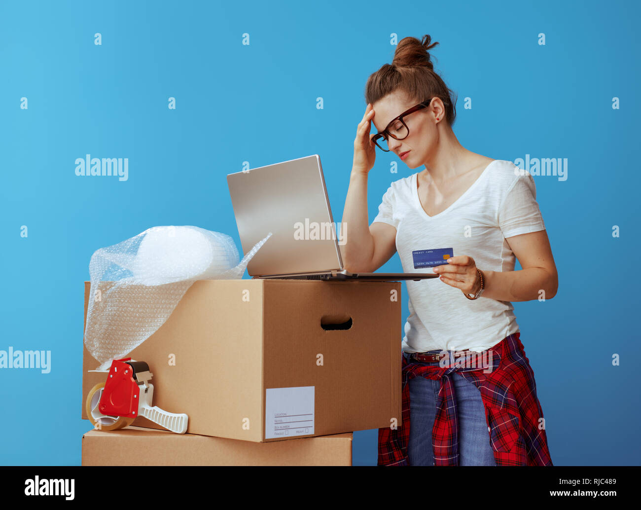 stressed modern woman in white t-shirt near cardboard box with laptop and credit card isolated on blue background - Stock Image